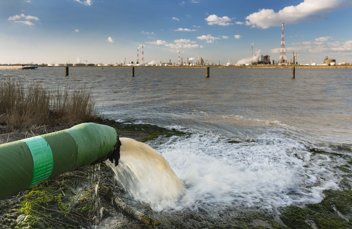 A wastewater pipe and a large oil refinery in the harbor of Antwerp, Belgium with blue sky and warm evening light.
